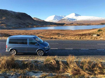 VW camper van with mountains in the background